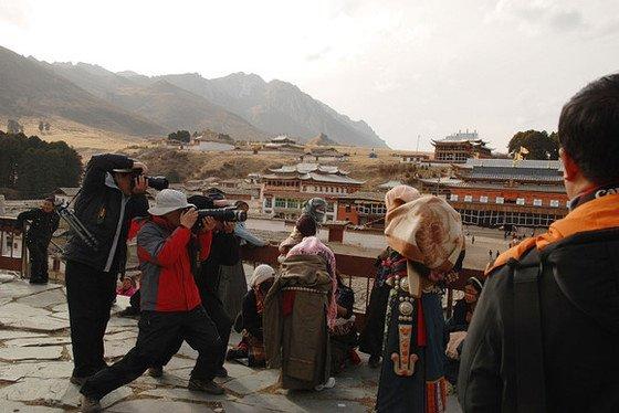 """地點:四川郎木寺左手邊山坡上的廟前描述:沿著右手走不了幾步,映入眼簾的場景背著孩子的藏族女人,被三個""""影友""""直面拍,請特別注意欄杆邊站著的藏族姑娘"""