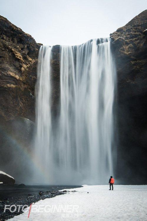 細小的人物突出了宏偉的瀑布。